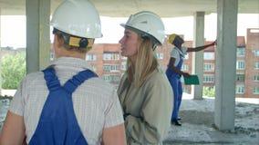 Ung arkitektur och kvinnlig arbetare som talar på konstruktionsplatsen för öppen luft arkivfilmer