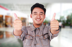 Ung asiat Guy Showing Two Thumbs Up arkivbilder
