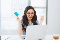 Ung asiatisk affärskvinna som använder kreditkorten för on-line betalning arkivfoto