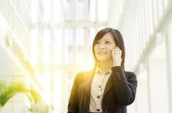 Ung asiatisk affärskvinna som kallar på telefonen Arkivfoton