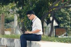 Ung asiatisk affärsman i formella kläder genom att använda bärbara datorn för hans jobb på parkera under morgontid royaltyfri foto