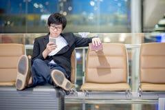 Ung asiatisk affärsman som använder smartphonen i flygplatsterminal Royaltyfri Bild
