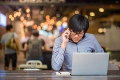 Ung asiatisk affärsman som arbetar i kafé Arkivfoto