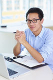 Ung asiatisk affärsman som arbetar i kontoret Arkivbild