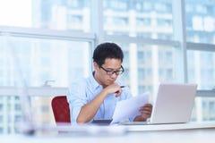 Ung asiatisk affärsman som arbetar i kontoret Arkivfoton