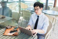 Ung asiatisk affärsman som arbetar på datoren, medan stå i ou Royaltyfri Fotografi