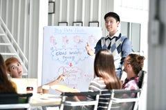 Ung asiatisk affärsman som ger presentation på framtida plan till hans kollegor arkivfoto