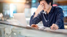 Ung asiatisk affärsman som känner sig stressad, medan arbeta med varven arkivfoton