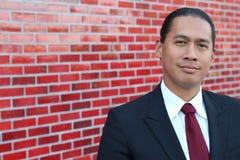 Ung asiatisk affärsman som ler att stå inomhus med kopieringsutrymme på vänstra sidan av bilden arkivfoto