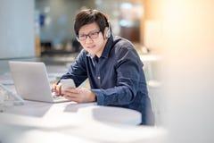 Ung asiatisk affärsman som lyssnar till musik, medan arbeta med l fotografering för bildbyråer