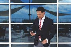 Ung asiatisk affärsman som rymmer hans mobiltelefon, medan stå på kontorsbyggnadfönstret utomhus arkivbild