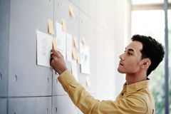 Ung asiatisk affärsmanWorking i regeringsställning mötesrum Koncentrat på dokumentanmärkning på väggen arkivfoto