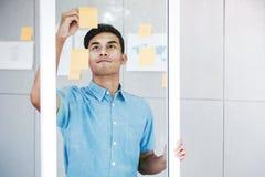 Ung asiatisk affärsmanWorking i regeringsställning mötesrum Man som analyserar dataplan och projekt Koncentrat på dokumentanmärkn royaltyfria bilder