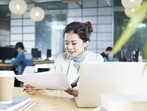 Ung asiatisk affärskvinna som i regeringsställning arbetar Royaltyfria Bilder