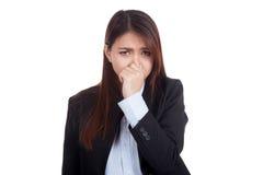 Ung asiatisk affärskvinna som rymmer hennes näsa på grund av en dålig smel Royaltyfri Fotografi