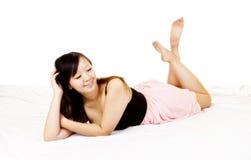 Ung asiatisk amerikansk kvinna som vilar klänningrosa färger Arkivbild