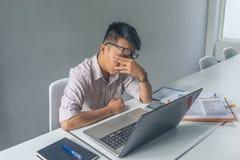 Ung asiatisk anställd att känna sig trött och frustrerat med jobb arkivfoton