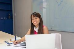 Ung asiatisk anställd som ler på arbetsplatsen Arkivbilder