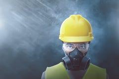 Ung asiatisk arbetare med den gula hjälmen och den skyddande maskeringen arkivfoto