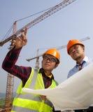 Ung asiatisk arkitektdiskussionsframdel av konstruktionsplatsen Royaltyfria Bilder