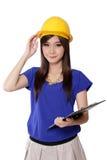 Ung asiatisk arkitektkvinna som rymmer hennes gula säkerhetshjälm, på vit Arkivfoton
