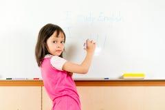 Ung asiatisk barnhandstil på en whiteboard Royaltyfria Bilder