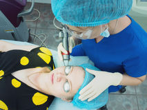 Ung asiatisk doktorskvinna som gör till patientlaser hud som resurfacing i estetisk medicin arkivfoto