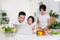 Ung asiatisk familj som tillsammans använder datoren hemma Fotografering för Bildbyråer