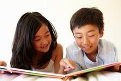 Ung asiatisk flicka- och pojkeläsebok royaltyfria foton