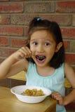 Ung asiatisk flicka som äter frukostsädesslag. Arkivfoton