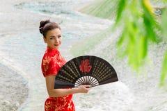 Ung asiatisk flicka som går i nationell klänning Arkivfoton