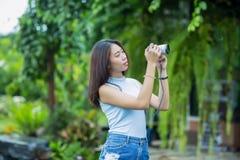 Ung asiatisk flicka som tar fotoet i trädgården Arkivbild