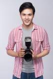 Ung asiatisk fotograf som rymmer den digitala kameran, medan arbeta I Royaltyfria Foton