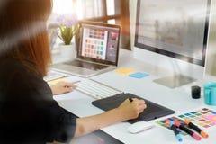 Ung asiatisk grafisk formgivare som arbetar på datoren arkivfoto