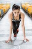 Ung asiatisk idrottskvinna i startande position på stadiontrappa Arkivbilder