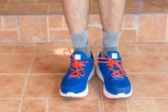 Ung asiatisk idrottsman nenman som framme binder huset för rinnande skor, man Arkivfoton