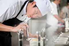 Ung asiatisk kockpläteringmat i en restaurang royaltyfri fotografi