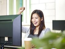 Ung asiatisk kontorsdam som är upphetsad på goda nyheter royaltyfri foto