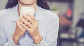Ung asiatisk kvinna för Closeup som dricker kaffe och leende i morgonen på kafét Arkivfoton