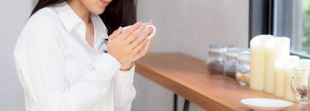 Ung asiatisk kvinna för Closeupbanerwebsite som dricker kaffe och leende i morgonen på kafét arkivfoton