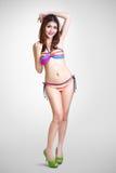 Ung asiatisk kvinna för nätt baddräktmode som poserar på grå backgro Arkivbilder