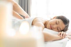 Ung asiatisk kvinna i brunnsortsalongen som får massage arkivfoton