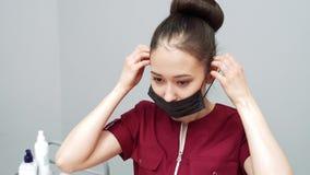 Ung asiatisk kvinna i likformign som bär en skyddande maskering och handskar stock video