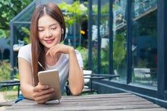 Ung asiatisk kvinna i tillfällig kläder som sitter utomhus- lyssna till Royaltyfri Fotografi