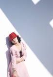 Ung asiatisk kvinna med den röda hatten som ligger mot väggen royaltyfri fotografi