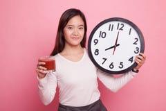 Ung asiatisk kvinna med den tomatfruktsaft och klockan Royaltyfria Foton