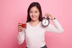 Ung asiatisk kvinna med den tomatfruktsaft och klockan Royaltyfri Bild