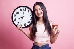 Ung asiatisk kvinna med den tomatfruktsaft och klockan Arkivbild