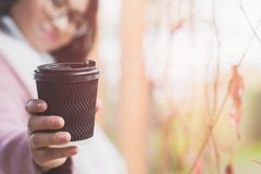 Ung asiatisk kvinna med den varma drinken arkivfoto