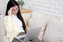 Ung asiatisk kvinna med frustrerat uttryck, medan arbeta med royaltyfri bild